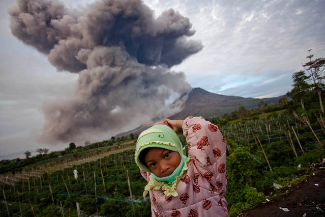 A girl stands in the foreground as Mount Sinabung spews pyroclastic smoke on January 8, 2014 in Karo District, North Sumatra, Indonesia. (Photo by Ulet Ifansasti/Getty Images)