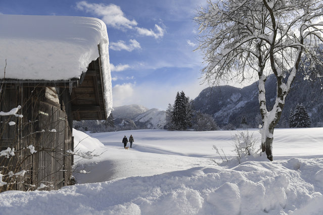 Two woman make their way through the fresh snow in Lofer, Austrian province of Salzburg on Friday, January 11, 2019. (Photo by Kerstin Joensson/AP Photo)