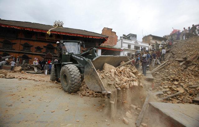 An earthmover removes debris at Durbar Square after an earthquake in Kathmandu, Nepal, Saturday, April 25, 2015. (Photo by Niranjan Shrestha/AP Photo)