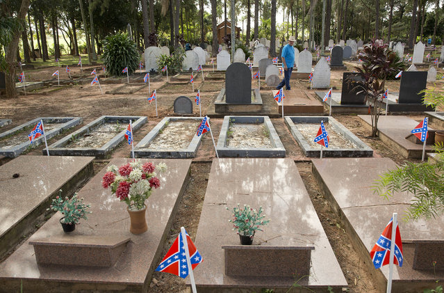 A man walks in a cemetery where American Southern immigrants are buried in tombs adorned with the confederate flag, during a party to celebrate the 150th anniversary of the end of the American Civil War in Santa Barbara d'Oeste, Brazil, Sunday, April 26, 2015. (Photo by Andre Penner/AP Photo)