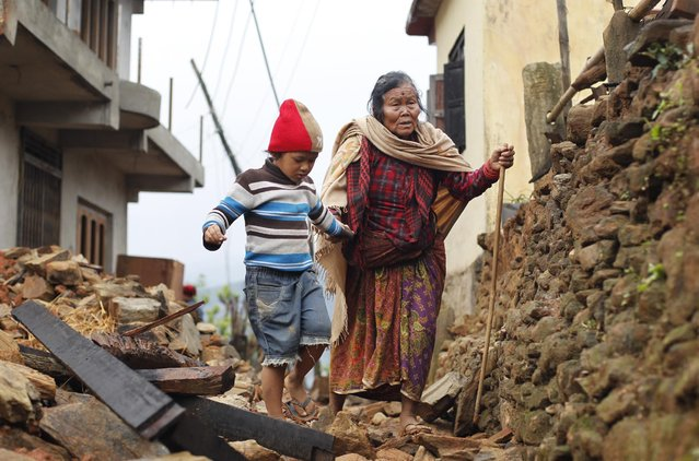 Jagot Kumari Rana, 79, is led through the rubble of collapsed homes by her grandson Sogat Rana, 7, in Paslang village near the epicenter of Saturday's massive earthquake in the Gorkha District of Nepal, Tuesday, April 28, 2015. (Photo by Wally Santana/AP Photo)