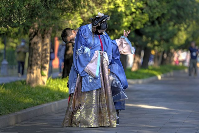 A man helps his partner on the traditional costume as they visit to the Temple of Heaven during the last day of the week-long China's National Day in Beijing, Thursday, October 7, 2021. (Photo by Andy Wong/AP Photo)