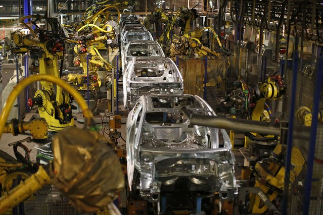A view shows the automobile assembly line as robots work on the construction of Peugeot 208, Citroen C3 and DS 3 cars at the PSA Peugeot Citroen plant in Poissy, near Paris, France, April 29, 2015. (Photo by Benoit Tessier/Reuters)