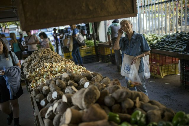 In this February 14, 2019 photo, a customer looks up at a price board at a farmers market in the middle-class district of Los Dos Caminos, in Caracas, Venezuela, in Caracas, Venezuela. Some Venezuelans manage to endure the nation's economic meltdown by clinging to the shrinking number of well-paid jobs or by receiving some of the hundreds of millions of dollars sent home by friends and relatives abroad. (Photo by Rodrigo Abd/AP Photo)