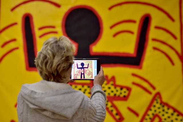 "A visitor takes a photo in the exhibition ""Keith Haring – The Political Line"" in Munich, Germany, April 30, 2015. The mostly large-format pictures and objects are on display in the Kunsthalle of the Hypo-Cultural Foundation until August 30. The US artist left most of his work untitled. (Photo by Peter Kneffel/EPA)"