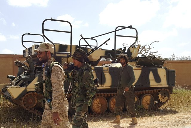 Members of forces loyal to Libya's eastern government walk next to an armoured vehicle during clashes with the Shura Council of Libyan Revolutionaries, an alliance of former anti-Gaddafi rebels who have joined forces with Islamist group Ansar al-Sharia, in Benghazi, Libya, March 12, 2016. (Photo by Reuters/Stringer)