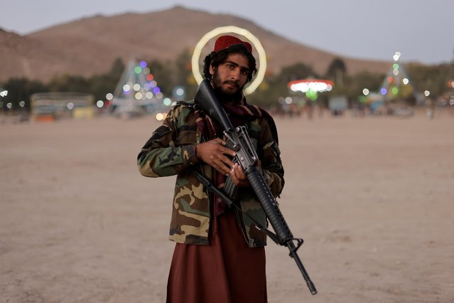Taliban fighter, Mostashhed from Wardak province, looks on as he visits Kabul for the first time as hundreds of Taliban fighters take a day off to visit the amusement park at Kabul's Qargha reservoir, at the outskirts of Kabul, Afghanistan on October 8, 2021. (Photo by Jorge Silva/Reuters)