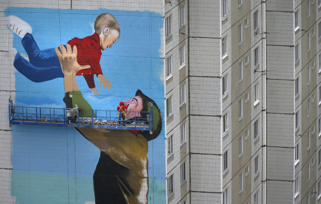 Russian artists paint a huge graffiti showing a Soviet soldier with a boy on the wall of an apartment house in Odintsovo, Moscow region, Russia, 29 April 2015. This year, Russia celebrates the 70th anniversary of the victory over Nazi Germany. (Photo by Sergei Ilnitsky/EPA)