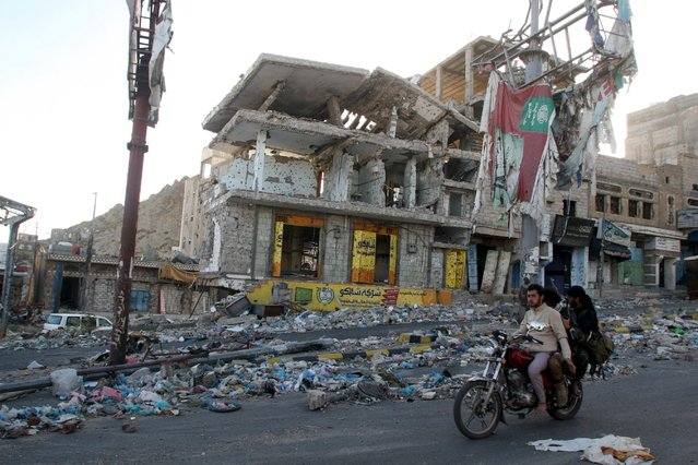 People ride on a motorbike past a building destroyed during recent fighting in Yemen's southwestern city of Taiz March 14, 2016. (Photo by Anees Mahyoub/Reuters)
