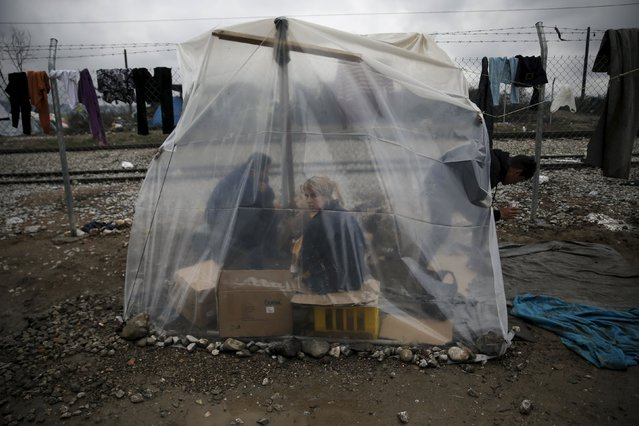 A migrant woman holding a baby is protected from rain under a plastic cover at a makeshift camp at the Greek-Macedonian border, near the village of Idomeni, Greece March 15, 2016. (Photo by Alkis Konstantinidis/Reuters)