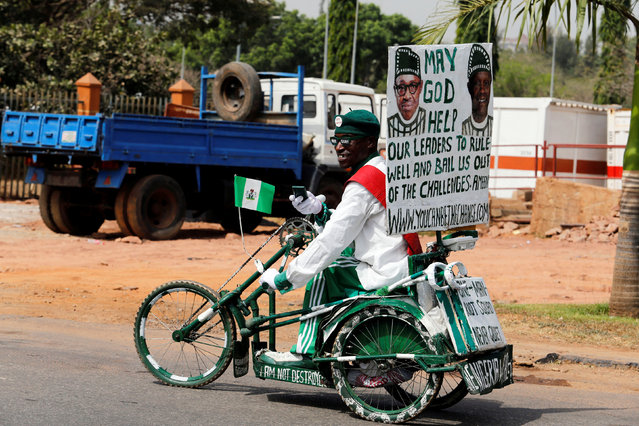 A man rides his tricycle with placards as he takes part in a rally to show support for Nigeria's President Muhammadu Buhari in Abuja, Nigeria Febuary 6, 2017. (Photo by Afolabi Sotunde/Reuters)