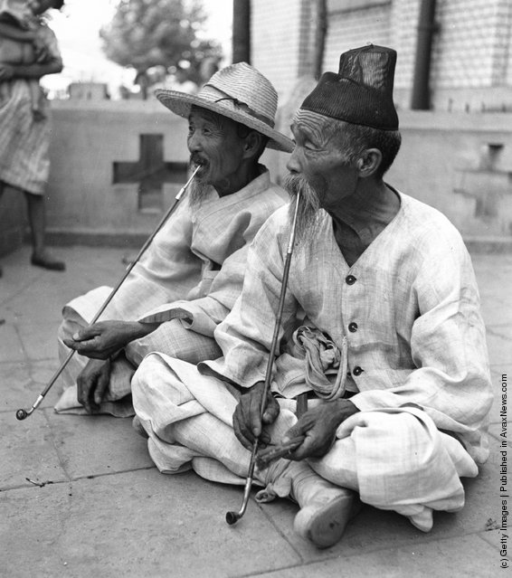 August 1950:  Two elderly men smoking pipes of opium on a terrace in Korea