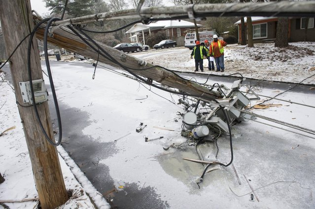 A crew asses the situation in front of a downed transformer smashed in the road during a winter storm on Wednesday, February 12, 2014, in Doraville, Ga. About 175,000 customers were without power Wednesday afternoon, power companies reported. (Photo by John Amis/AP Photo)