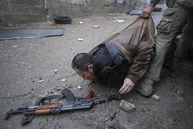 Syrian rebels help evacuate a comrade who was hit by sniper fire as the group prepared an attack on a government controlled army checkpoint in the Ain Tarma neighborhood of Damascus on January 30, 2013. (Photo by Goran Tomasevic/World Press Photo)