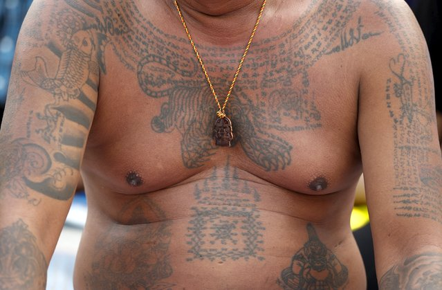 A devotee's tiger tattoo and amulets are pictured during the annual Magic Tattoo Festival at Wat Bang Phra in Nakhon Pathom province, on the outskirts of Bangkok, Thailand, March 19, 2016. (Photo by Chaiwat Subprasom/Reuters)