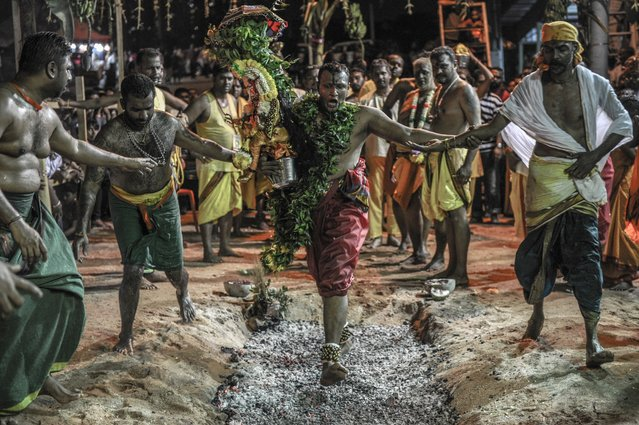 "This photo taken on May 3, 2015 shows a Malaysian Hindu devotee (C) carrying an idol walking on hot coals during a firewalking festival at a temple in Kuala Lumpur. Firewalking or ""Thimithi"" is a festival originating in southern India that is celebrated in honour of Draupadi, who is considered the incarnation of Mariamman. (Photo by Mohn Rasfan/AFP Photo)"
