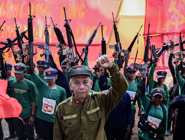"""Jaime """"Ka Diego"""" Padilla (C), spokesperson of the Melito Glor Command of the New People's Army (NPA) raises his fist along side his comrades during their 50th founding anniversary celebration at an undisclosed location in the mountains of Sierra Madre, Philippines, 31 March 2019. (Photo by Alecs Ongcal/EPA/EFE)"""