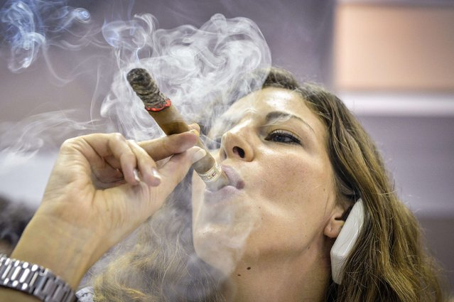 A woman smokes a cigar during the competition for the longest ash in Havana, on February 27, 2014. Cigar enthusiasts from around the world come to Cuba during the annual Cigar Festival to visit tobacco farms and factories and savor new cigar brands. (Photo by Ramon Espinosa/Associated Press)