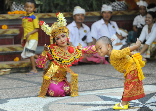 This picture taken on February 9, 2019 shows young Balinese dancers performing during an agung ceremony, held every six months in honour of their ancestors and deities, at Pererepan Sari Pedungan in Denpasar, Indonesia's Bali island. (Photo by Sonny Tumbelaka/AFP Photo)