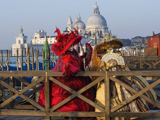 Two women dressed in Carnival Costumes pose in Saint Mark's Square on February 25, 2014 in Venice, Italy. The 2014 Carnival of Venice will run from February 15 to March 4 and includes a program of gala dinners, parades, dances, masked balls and music events. (Photo by Marco Secchi/Getty Images)