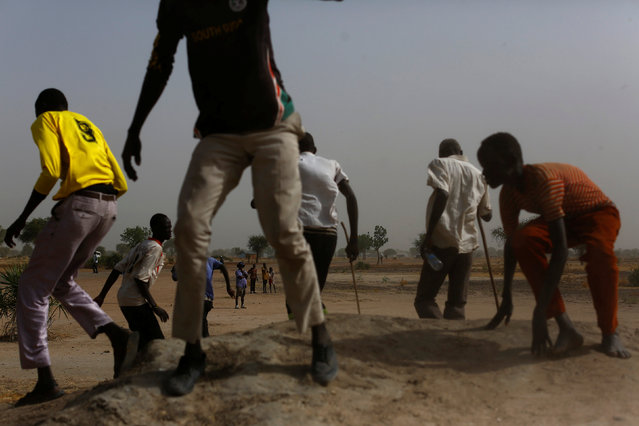 People move away from as a United Nations World Food Programme (WFP) helicopter lands in Rubkuai village, Unity State, northern South Sudan, February 17, 2017. (Photo by Siegfried Modola/Reuters)