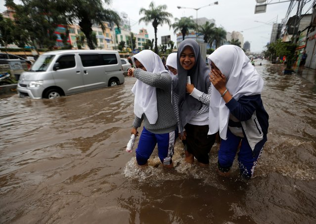 Students wade through floodwaters after school in a flood-hit area at the Mangga Dua business district in Jakarta, Indonesia February 21, 2017. (Photo by Reuters/Beawiharta)