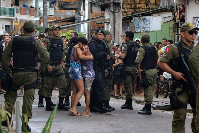 Residents mourn surrounded by police officers outside a bar as corpses are removed after a shooting, in Belem, Para state, Brazil on May 19, 2019. At least 11 people were shot dead Sunday at a bar in northern Brazil when unknown men opened fire, Para state Public Security Secretariat informed. (Photo by Claudio Pinheiro/AFP Photo)