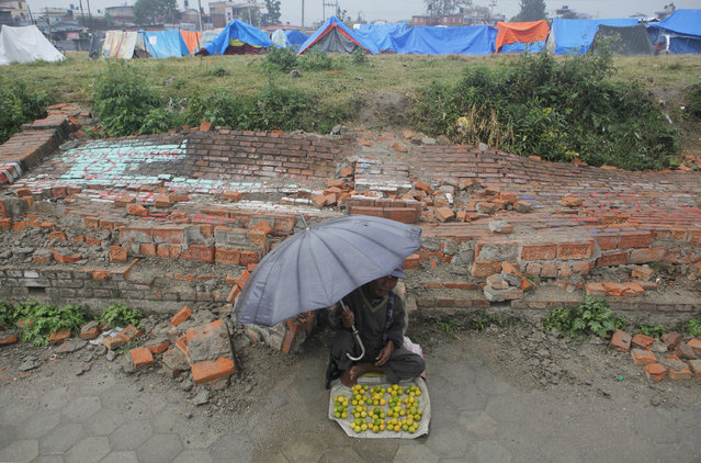 A Nepalese street vendor waits for the customers in front of a broken wall, as makeshift tents for those whose houses were damaged by the earthquake stand in the background,  in Kathmandu, Nepal, Saturday, May 9, 2015. (Photo by Niranjan Shrestha/AP Photo)