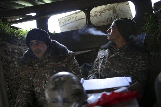 Ethnic Armenian fighters Avanesyan Vahe, 27, left, and Gasparyan Harutyun, 19, rest at their artillery positions at Martakert province in the separatist region of Nagorno-Karabakh, Azerbaijan, Monday, April 4, 2016. (Photo by Vahan Stepanyan/PAN Photo via AP Photo)