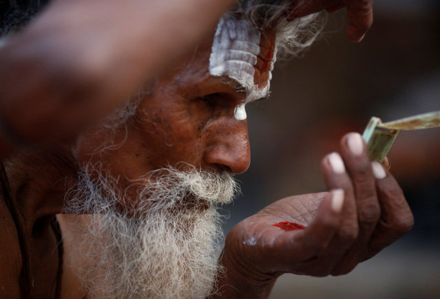 A Hindu holy man, or sadhu, applies tika on his forehead at the premises of Pashupatinath Temple during the Shivaratri festival in Kathmandu, Nepal February 24, 2017. (Photo by Navesh Chitrakar/Reuters)