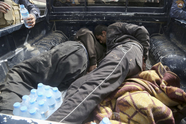 Iraqi Federal police take two handcuffed suspected Islamic State militants for interrogation after they were arrested inside their home on the western side of Mosul, Iraq, Monday, February 27, 2017. (Photo by Khalid Mohammed/AP Photo)