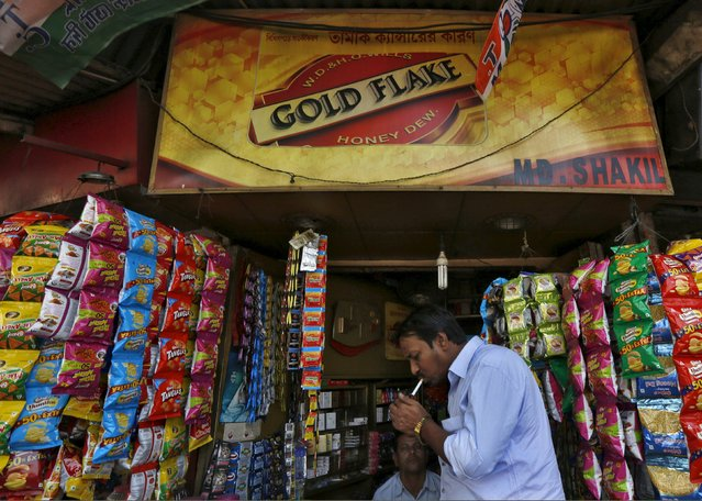 A man lights a cigarette in front of a kiosk in Kolkata, India, April 7, 2016. (Photo by Rupak De Chowdhuri/Reuters)