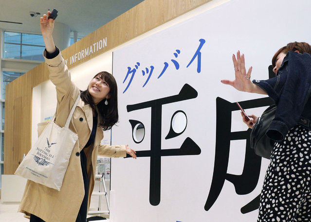 """Visitors take a selfie with a panel with """"Good-bye Heisei"""" written in Japanese at Fukuoka Tower in Fukuoka, southwestern Japan, Tuesday, April 30, 2019. Japan's Emperor Akihito is set to abdicate later in the day as Japan embraces the end of his reign with an emotion mixed with reminiscence and hopes for a new era. (Photo by Miyuki Saito/Kyodo News via AP Photo)"""