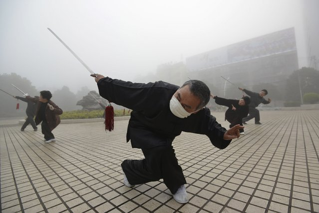A man wearing a mask does morning exercise on a hazy day in Fuyang, Anhui province, March 26, 2014. (Photo by Reuters/China Daily)