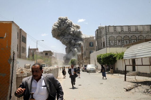 People flee as smoke billows after air strikes hit the house of Yemen's former President Ali Abdullah Saleh in Sanaa May 10, 2015. (Photo by Mohamed al-Sayaghi/Reuters)