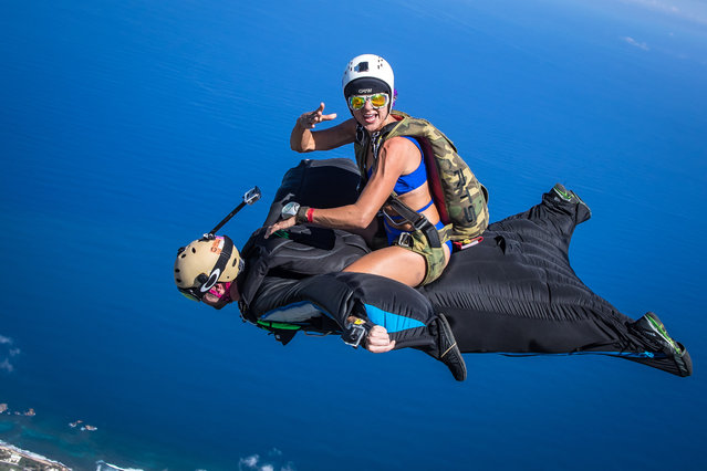 Robyn Young surfs on the back of Oliver Miller as they descend upon Arecibo, Puerto Rico. (Photo by Jeff Donohue/Caters News)