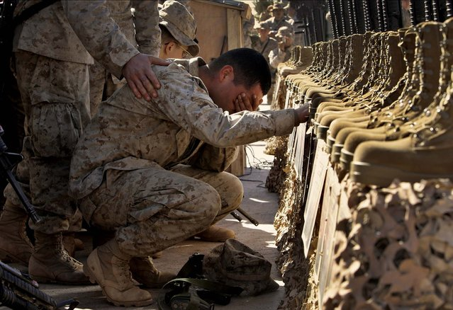A U.S. Marine cries during the memorial service for 31 killed U.S. servicemen at Camp Korean Village, near Rutbah, western Iraq, Feb. 2, 2005. (Photo by Anja Niedringhaus/AP Photo)