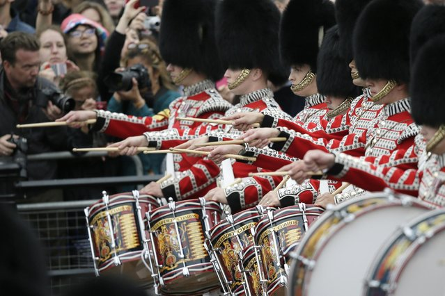 """Soldiers march during the Trooping The Colour parade at Buckingham Palace, in London, Saturday, June 13, 2015. Hundreds of soldiers in ceremonial dress have marched in London in the annual Trooping the Color parade to mark the official birthday of Queen Elizabeth II. The Trooping the Color tradition originates from preparations for battle, when flags were carried or """"trooped"""" down the rank for soldiers to see. (AP Photo/Tim Ireland)"""