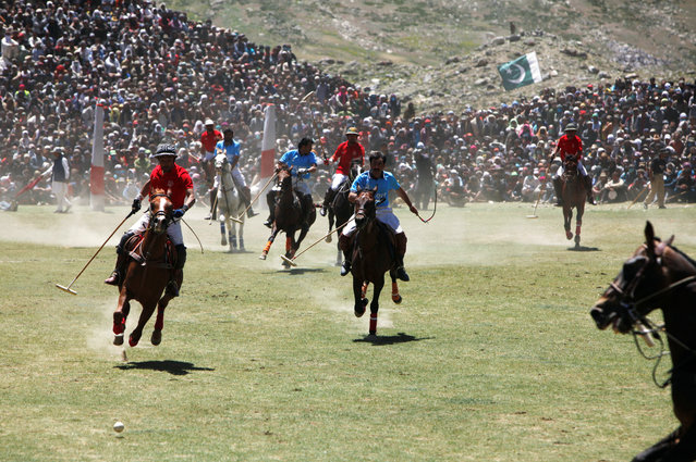Players (Chitral in Red and Gilgit-Baltistan in Blue) fight for the ball during the annual Shandur Polo Festival, at Shandur Pass, at an estimated altitude of around 3700 meters, in Chitral, Pakistan on July 9, 2019. (Photo by Khurram Parvez/Reuters)