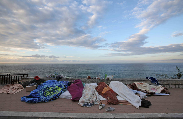Migrants sleep covered by blankets on the seawall at the Saint Ludovic border crossing on the Mediterranean Sea between Vintimille, Italy and Menton, France, June 17, 2015. Police on Tuesday began hauling away mostly African migrants from makeshift camps on the Italy-France border as European Union ministers met in Luxembourg to hash out plans to deal with the immigration crisis.   REUTERS/Eric Gaillard
