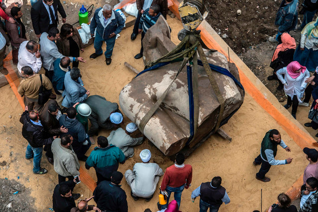 Egyptian workers excavate the statue, recently discovered by a team of German- Egyptian archeologists, in Cairo' s Mattarya district on March 13, 2017. (Photo by Khaled Desouki/AFP Photo)