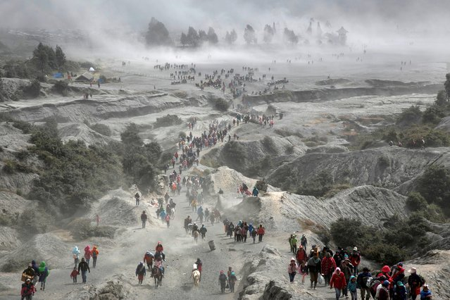 Tenggerese people and tourists gather near the Bromo volcano during the annual Kasada ceremony where Hindu worshippers had a ritual with throwing offerings such crops and livestock into the crater as thanks giving to their gods, in Probolinggo, East Java province, Indonesia, July 18, 2019. (Photo by Rizki Dwi Putra/Reuters)