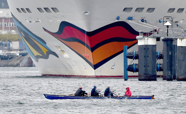 """Rowers pass by the bow of the cruise ship """"AIDAluna"""" at the Baltic Sea pier in Kiel, Germany, Monday, April 25, 2016. (Photo by Carsten Rehder/DPA via AP Photo)"""