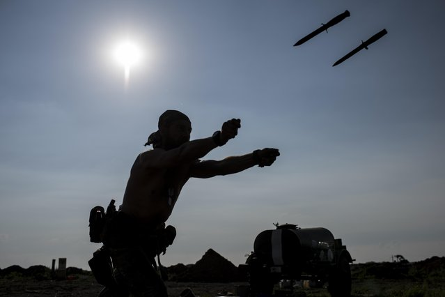 In this photo taken Monday, June 22, 2015, a Ukrainian soldier from the Kiev-2 volunteer battalion throws knifes during a training at the frontline in the village of Krymske, east Ukraine. (Photo by Evgeniy Maloletka/AP Photo)