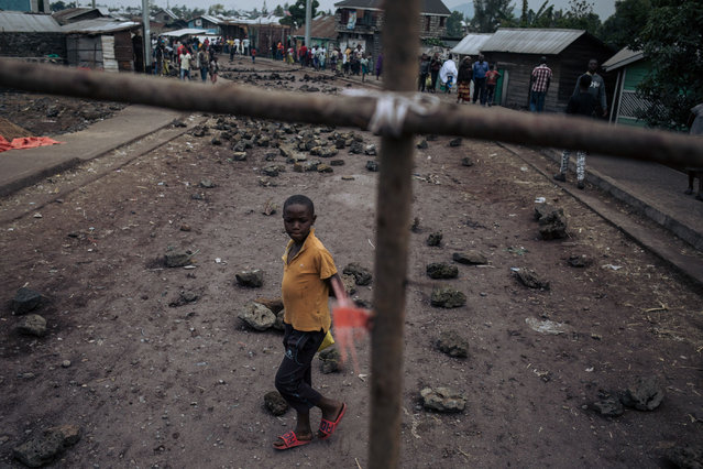 A boy crosses a roadblock in the Kilijiwe district of northern Goma, in the eastern Democratic Republic of Congo, on July 24, 2019. Residents of a neighbourhood in Goma, in the eastern Democratic Republic of Congo, barricaded roads on July 24, paralysing all activities, in protest against the killing of four people, including two teenagers, killed on the eve by armed bandits. (Photo by Alexis Huguet/AFP Photo)