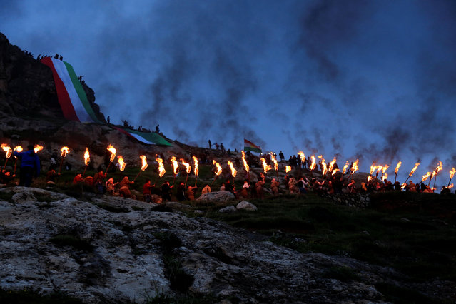 Iraqi Kurdish people carry fire torches up a mountain, as they celebrate Newroz Day, a festival marking their spring and new year, in the town of Akra, Iraq March 20, 2017. (Photo by Ari Jalal/Reuters)