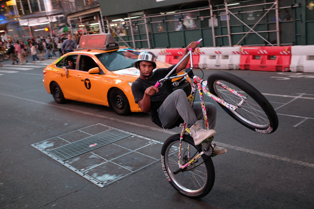 A youth rides his bicycle at Times Square, in New York City, U.S., August 14, 2019. (Photo by Lucas Landau/Reuters)
