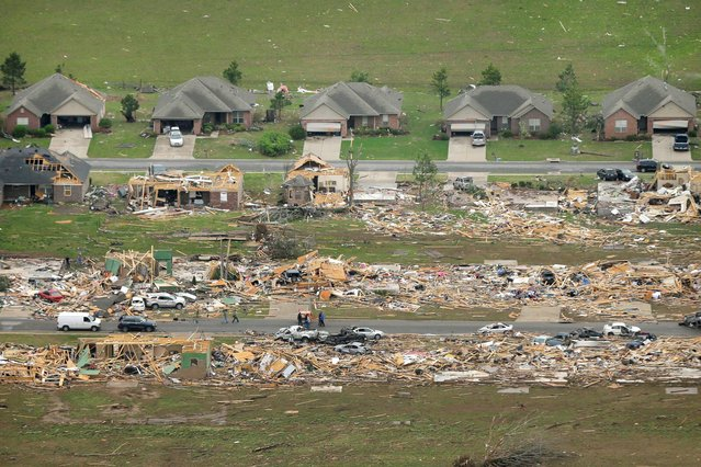 A row of lightly damages houses, top, face destroyed homes in a Vilonia, Ark., neighborhood Monday, April 28, 2014 after a tornado struck the town late Sunday, killing at least 16 people. (Photo by Danny Johnston/AP Photo)