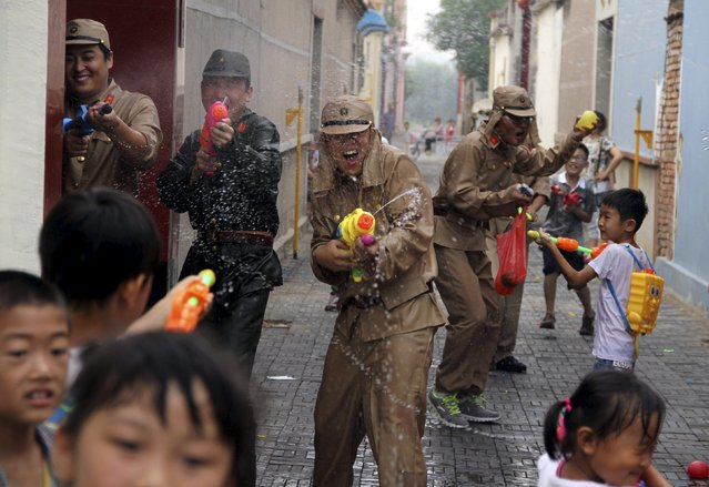 Staff of a tourism resort dressed as Japanese soldiers squirt water guns as they take part in a mock fight with children visitors during an event to mark the 70th anniversary of the end of the Sino-Japan War, in Binzhou, Shandong province, China, July 5, 2015. (Photo by Reuters/Stringer)