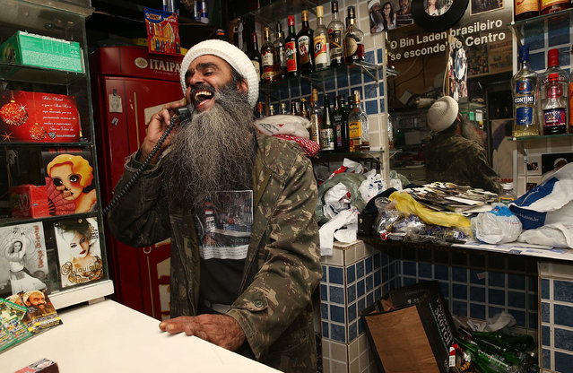 "Osama bin Laden lookalike Ceara Francisco Helder Braga Fernandes laughs while chatting on the phone in his ""Bar do Bin Laden"" on April 29, 2014 in Sao Paulo, Brazil. Braga says he was known as the ""Beard Man"" before 9/11 but became known as a Bin Laden lookalike following the 9/11 attacks. He says he is Christian and continues to play the role to support his business. (Photo by Mario Tama/Getty Images)"